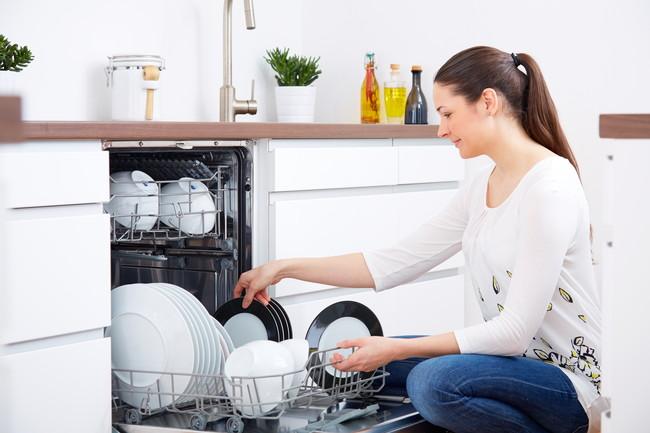 食器洗い乾燥機から食器を取り出している女性