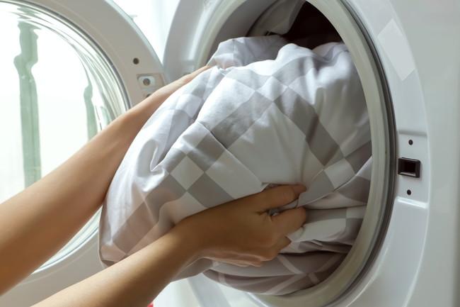 毛布を洗濯機に入れているところ