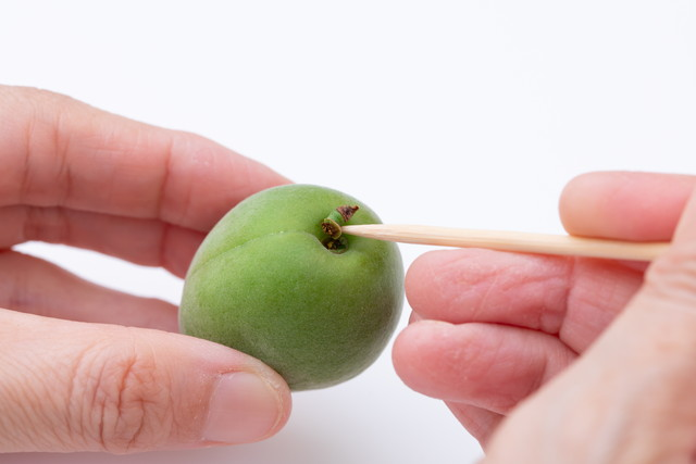 梅のヘタを竹串で取り除く様子