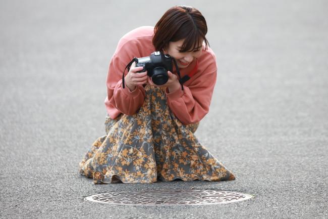 マンホールを撮影する女性