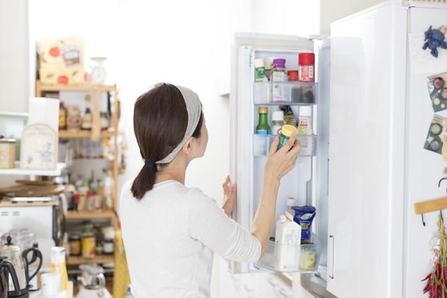 冷蔵庫を開ける人の後ろ姿