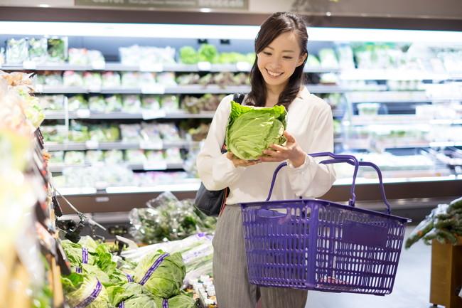スーパーでキャベツを選んでいる女性