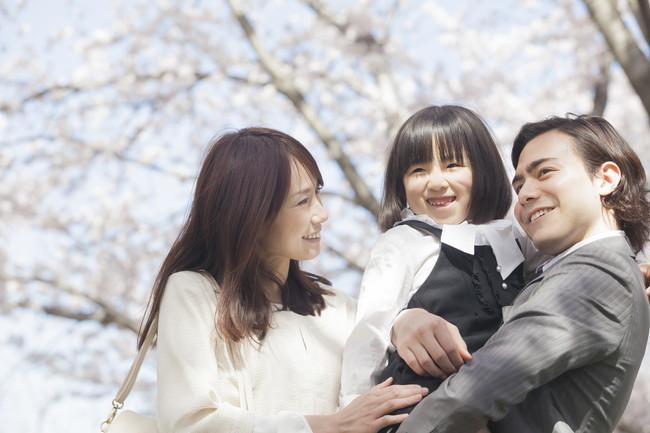 桜並木に立つ家族