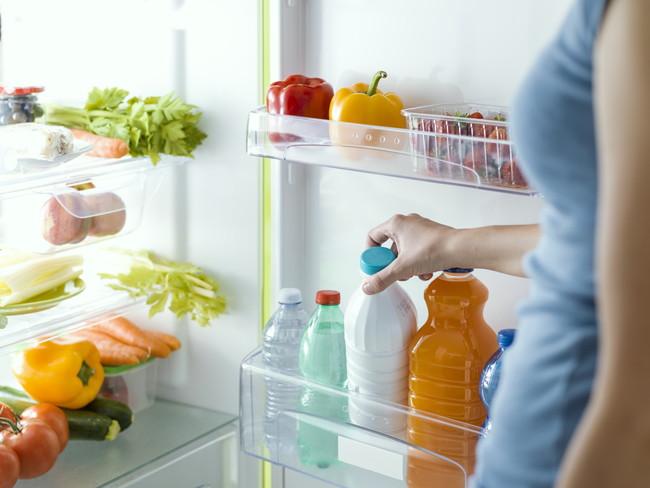 冷蔵庫から牛乳を取り出す女性