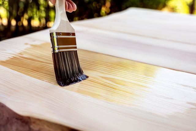 ヘアブラシとオイルで木製のテーブルのグレージング