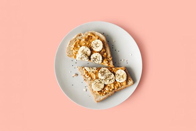 ピンクの背景、白い丸い皿に食パン、ナッツバターとバナナ