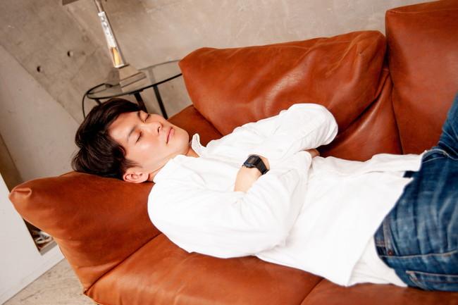 ソファで腕組をして寝る男性