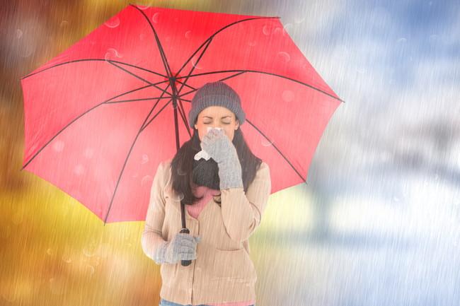 傘をさしながらくしゃみをしている女性