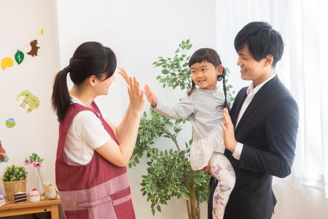 幼稚園教諭と手を振る親子