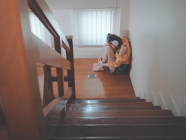 悲しみながら音楽を聴く女性