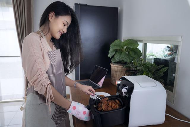 電気フライヤーで料理する女性