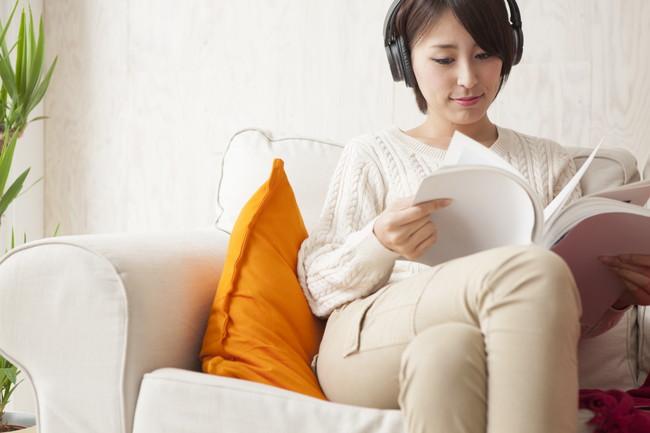 音楽を聴きながら本を読む女性