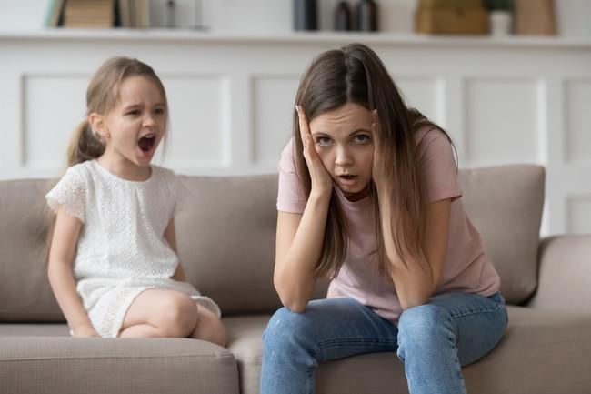 泣きじゃくる子供に頭を抱えている母親