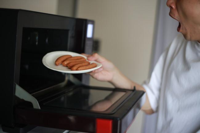ウインナーを紙皿に並べ電子レンジで温めようとする男性