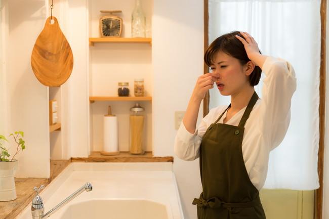 キッチンで鼻をつまんでいる女性