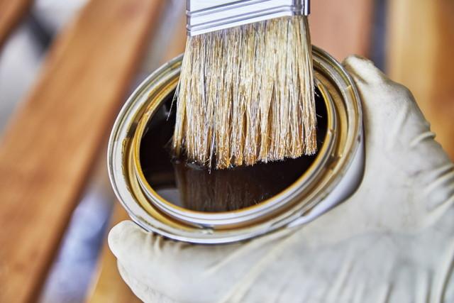 塗料の入った容器を持つ手(ゴム手袋)とハケ