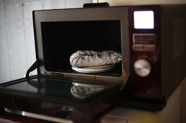 電子レンジの中のアルミホイルを巻いたサツマイモ