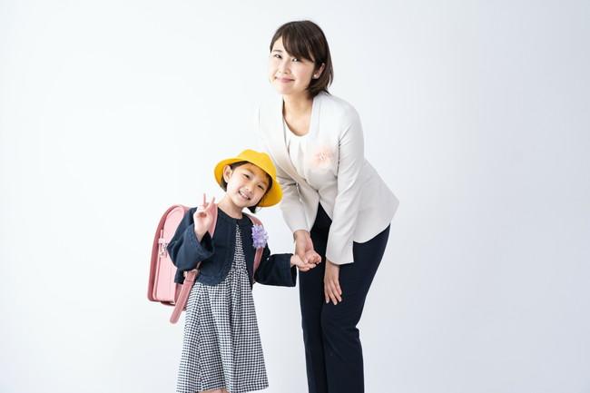 入学式でランドセル姿の女の子と母親