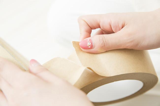 ガムテープを貼る女性の手元