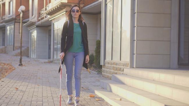 白杖で歩く女性
