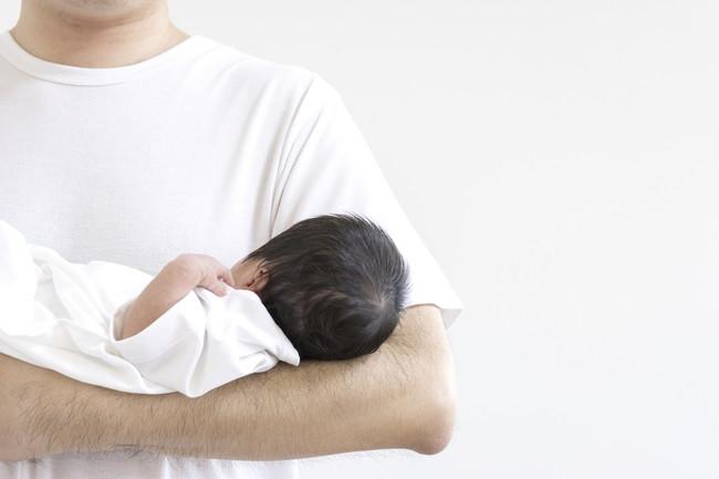 新生児を抱いている男性