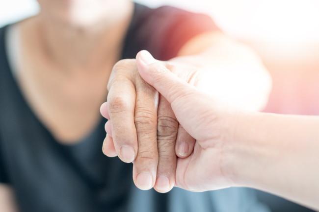 手を握ってサポートしている