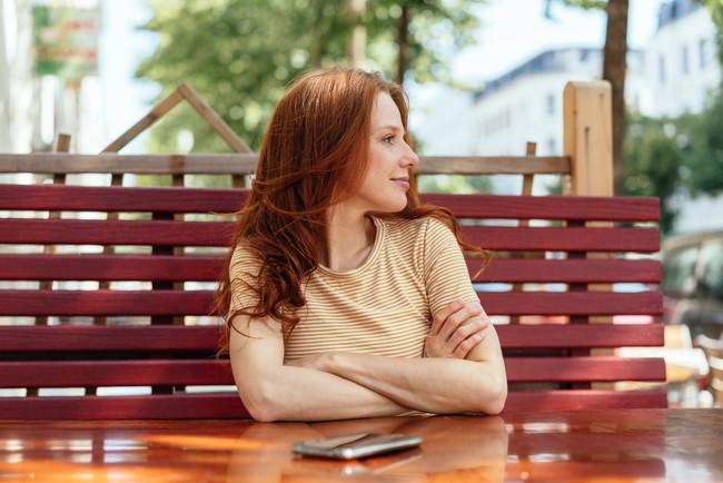 腕を組んで微笑みながら座っている女性