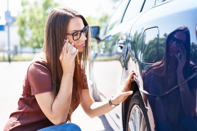 車の故障で電話をしている女性