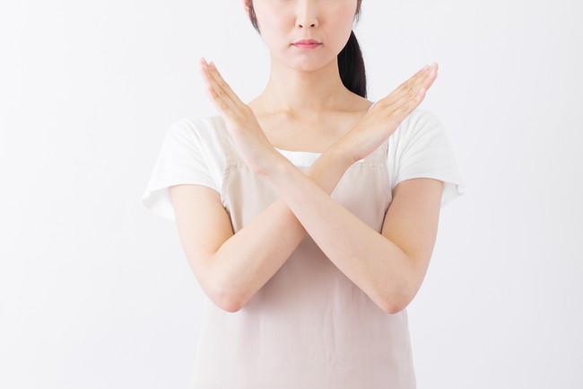 バツ印を示すエプロン姿の女性