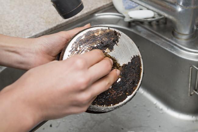 鍋の焦げ付きを磨く女性