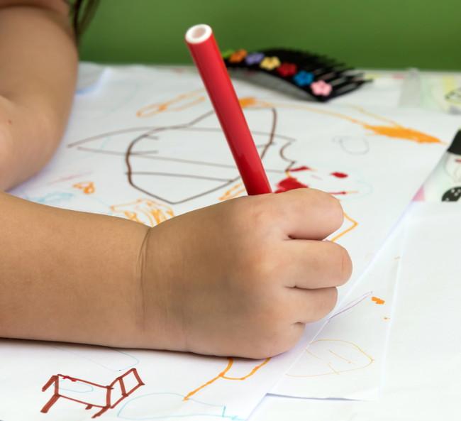 ペンを使ってお絵かきをしている子供