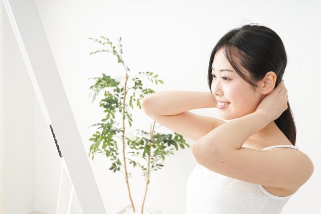 鏡の前で髪をまとめている女性