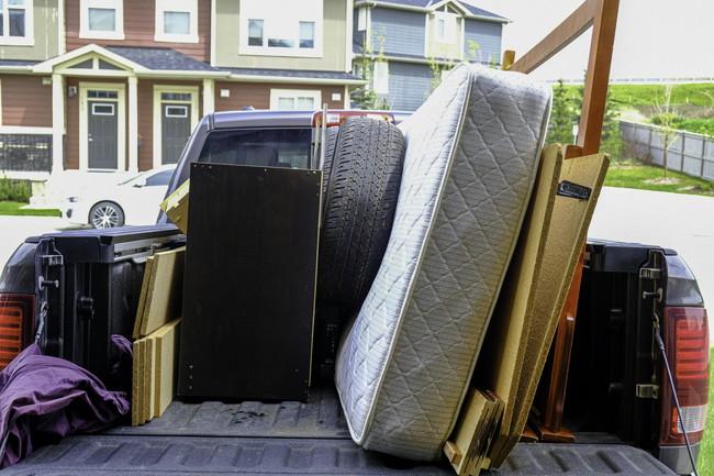 マットレスなどの粗大ごみを車に積んでいるところ
