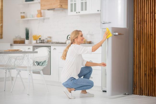 冷蔵kの扉を磨いている女性