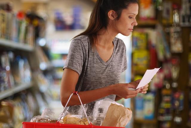 買い物リストをみて買い物する女性