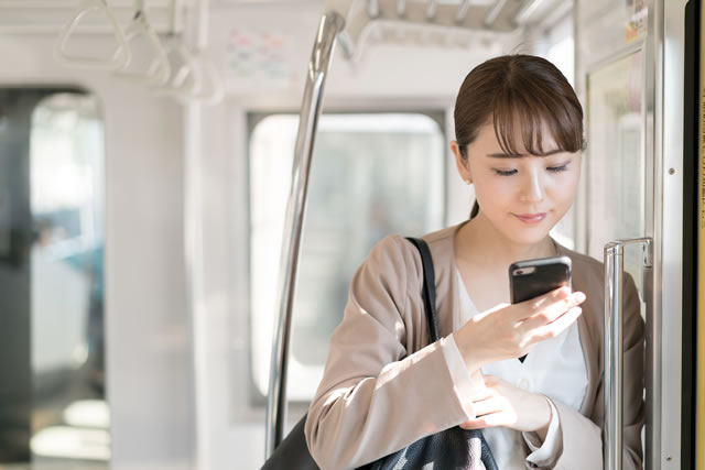 電車でソシャゲで遊ぶ女性