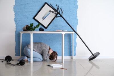 机の下に非難する人