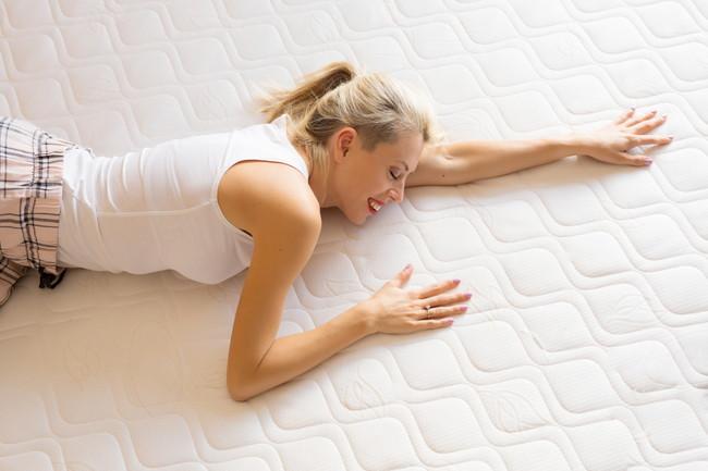 マットレスに寝転ぶ女性
