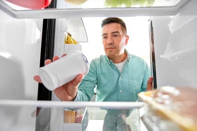 ヨーグルトを冷蔵庫に入れる男性