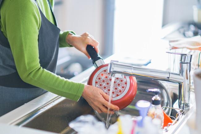 フライパンを洗う女性