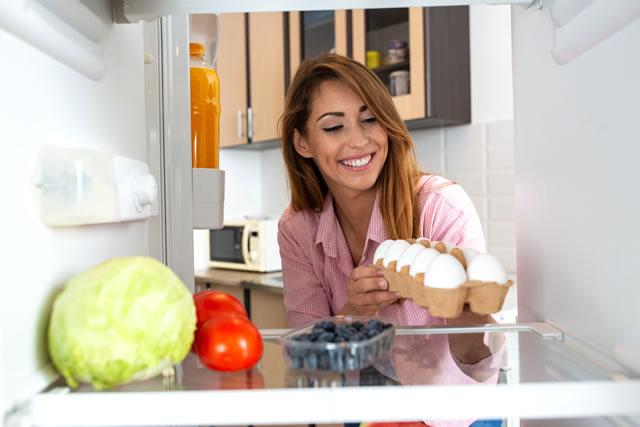 卵を冷蔵庫に入れる女性
