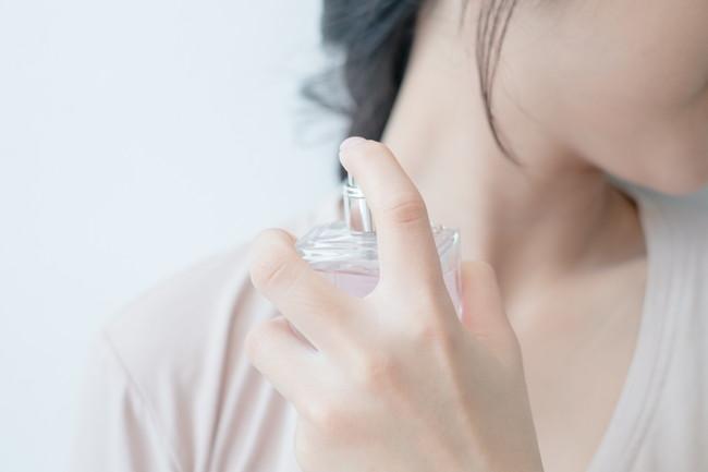 香水を首元に浸けている女性