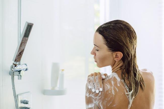 シャワーで体を洗っている女性