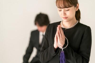 葬式・葬儀で礼拝する女性