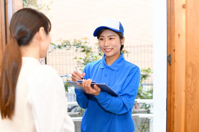 女性作業員が自宅玄関に訪問するイメージ