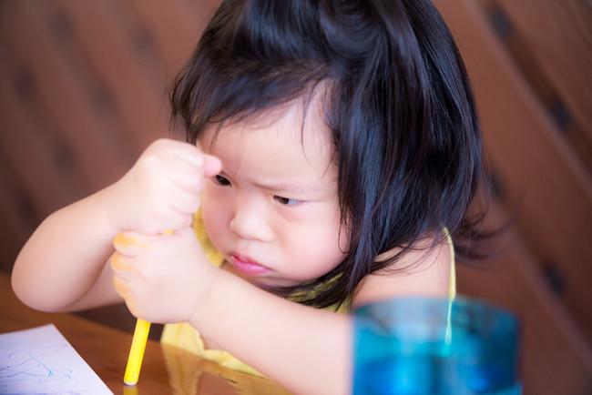ペンをにぎっている少女