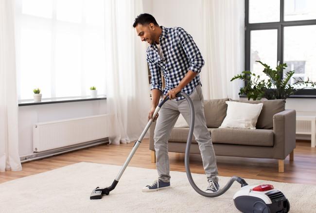 絨毯の上を掃除機をかけている男性