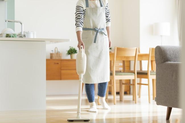 リビングルームの掃除機をかけている女性