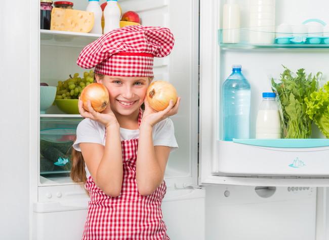 冷蔵庫の前で玉ねぎを持っている少女