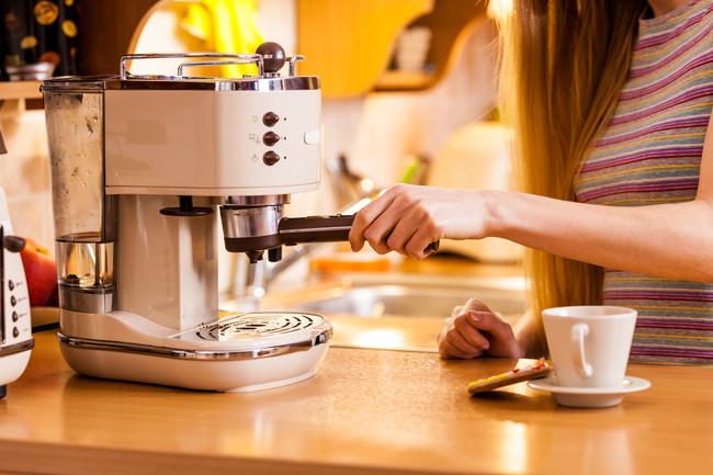 コーヒーメーカーを使用する女性